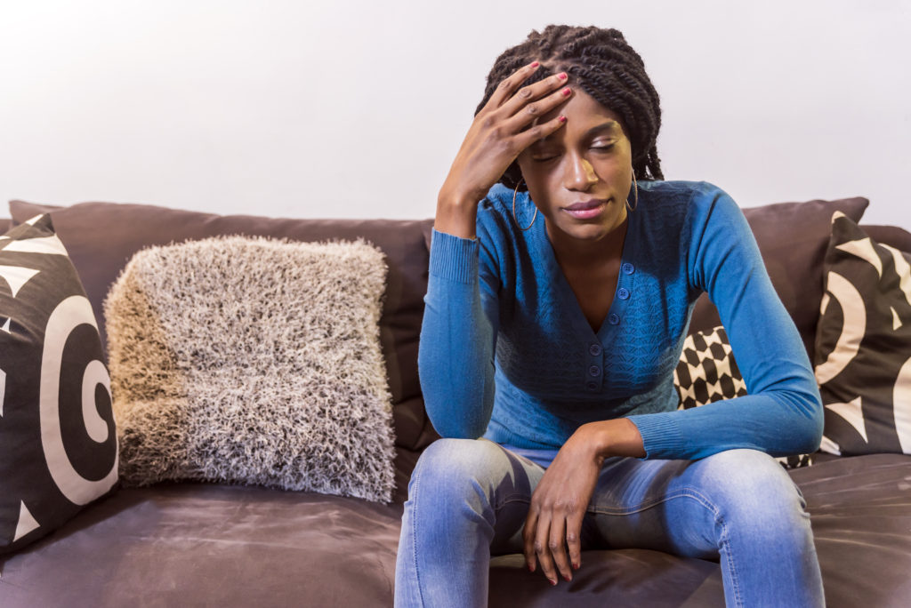 Portrait of sad dark-skinned female student with Afro haircut, sitting alone with unhappy boring expression on her face, Thoughtful woman sitting on bed at home in the bedroom, people, emotions, stress and health care concept - unhappy african american young woman touching her head and suffering from headache